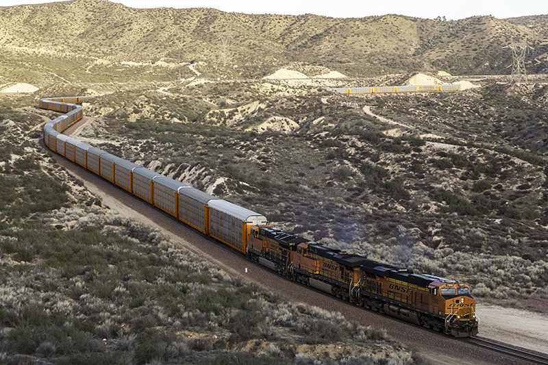 Autorack train winds through desert hillsides